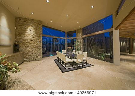Chairs around table on rug in spacious dining room at home
