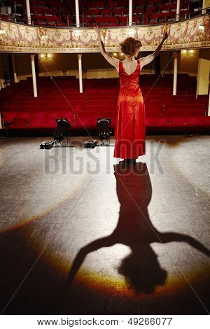 Full length rear view of a woman in red gown standing on stage floor