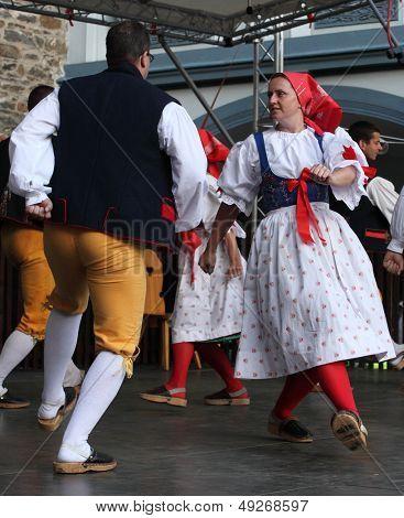 DOMAZLICE CZECH REPUBLIC - AUGUST 10: The Folklore Ensemble Usmev (Smile) dressed in traditional Czech (Pilsen) garb dancing and singing on The Chodske slavnosti medieval market on August 10, 2013.
