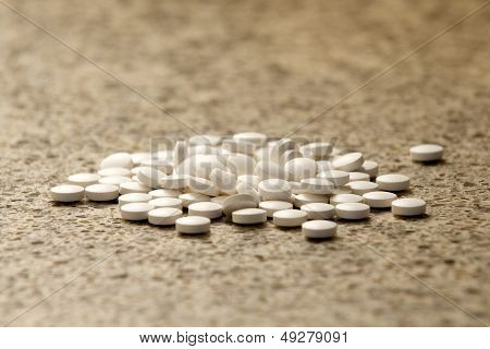 Pile Of Generic White Pills On Hard Surface