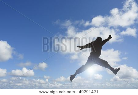 Silhouette Of Man Jumping Over Sun.