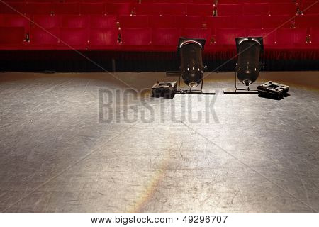 View of an empty stage with spotlights and red seats