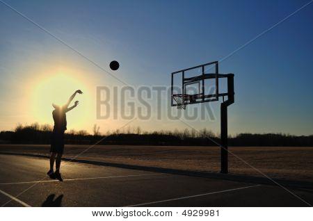 Silhouette Of Teen Boy Shooting A Basketball