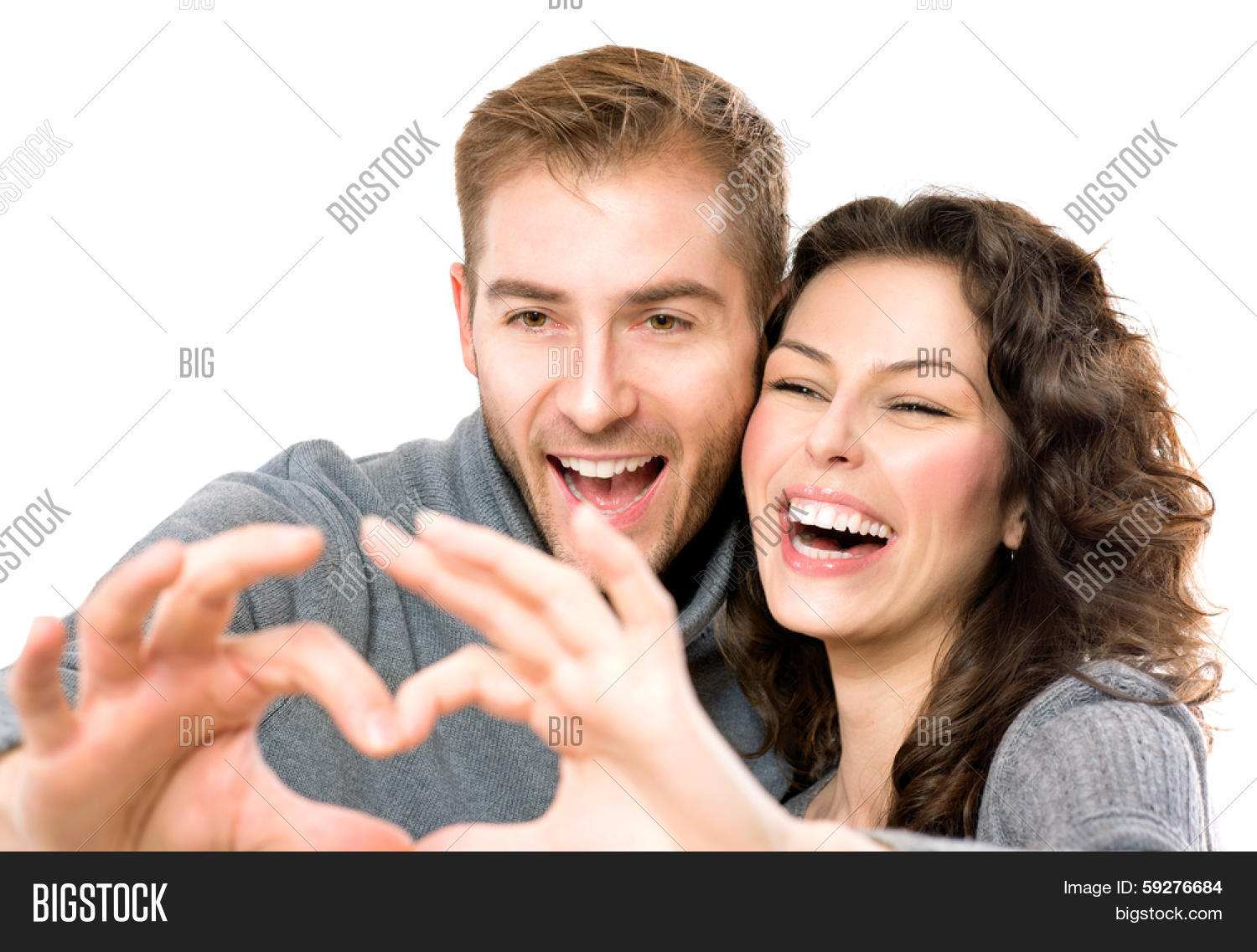 Valentine Couple isolated on white background. Portrait of Smiling Beauty Girl and her Handsome Boyfriend making shape of Heart by their Hands. Happy Joyful Family. Heart Sign. Valentines Day
