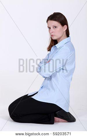 woman kneeling down cross-armed looking sulky