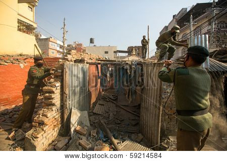 KATHMANDU, NEPAL - DEC 24: Unknown nepalese police during a operation on demolition of residential slums, Dec 24, 2013 in Kathmandu, Nepal. In KTM is home to 50,000 squatters spread across city slums.