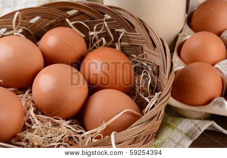 Closeup of a basket full of brown eggs in a rustic farmhouse like setting. Horizontal format with shallow depth of field.