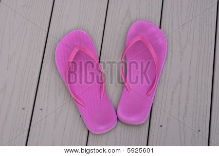 two pink summer flip flops by pool deck