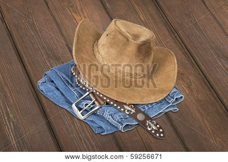 Cowboy hat and accessories over  wood plank background with clipping path. poster