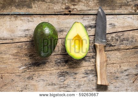 Whole and cut in half Avocado with Knife. Top View poster