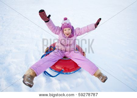 Child sledding in winter hill. Happy girl tobogganing