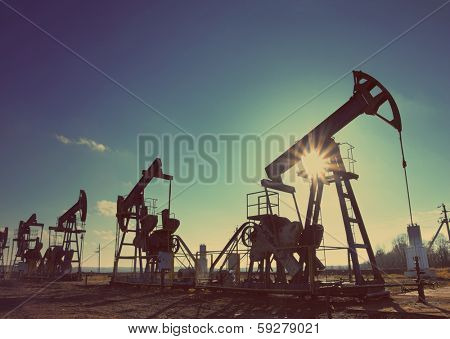 working oil pumps silhouette against sun - vintage retro style