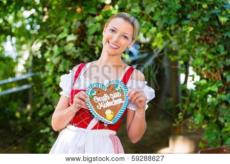 Young woman in traditional Bavarian clothes or tracht with a gingerbread souvenir heart in beergarden on Oktoberfest