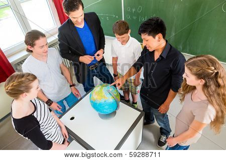 School Students or pupils or mates having group work while geography lesson and the teacher test or educate them in school or class