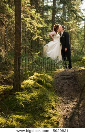 Bride And Groom Kissing In Fairy Tale Forest