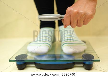 Woman Feet On Weighing Scales Looking Weight Over Magnifying Glass. Exaggerate With Weight Loss Conc