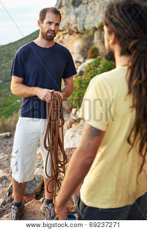 Friends preparing to go rock climbing and untangling the rope