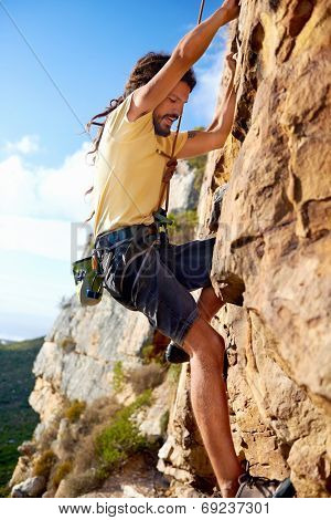 A dreadlock rock climbing guy finding a foothold on a steep mountain