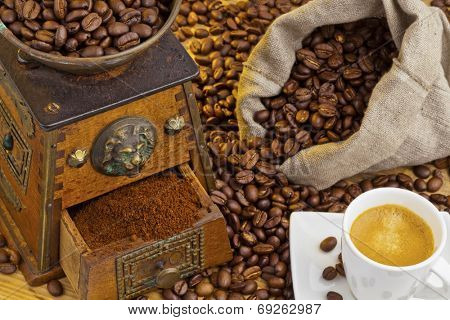many coffee beans are next to a coffee grinder. freshly ground coffee