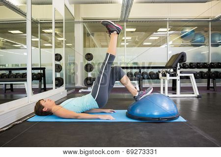 Fit brunette using bosu ball to work out at the gym