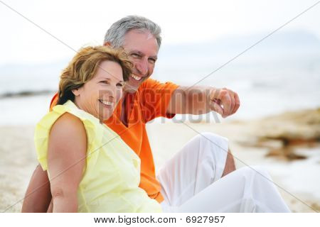 Mature couple sitting on the beach.
