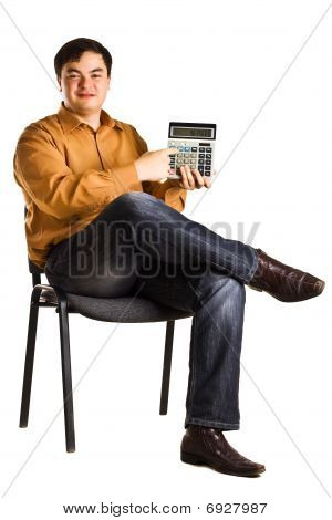 Young Man Sitting On A Chair Shows The Numbers On The Calculator