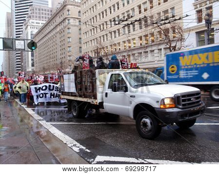 Truck Full Of Protester And Protesters Walking Behind Them Holds 'house Keys, Not Handcuff' Sign To