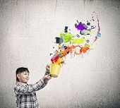 Cute boy splashing colorful paint from bucket poster
