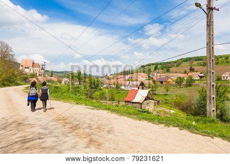 two female hikers walking on village road near Biertan in Transylvania Romania