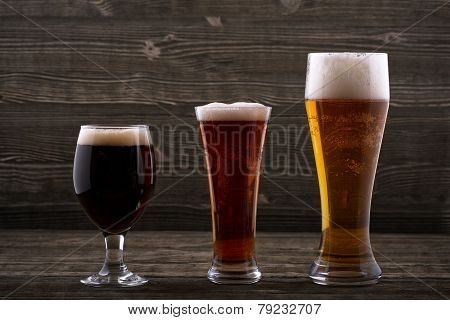 Various types of beer on a wooden background poster