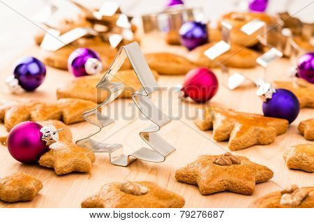 Christmas gingerbread cookies with cutters and christmas baubles.