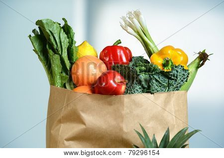 Assortment of fresh produce in grocery paper bag by window poster