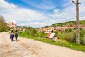 two female hikers walking on village road near Biertan in Transylvania Romania poster