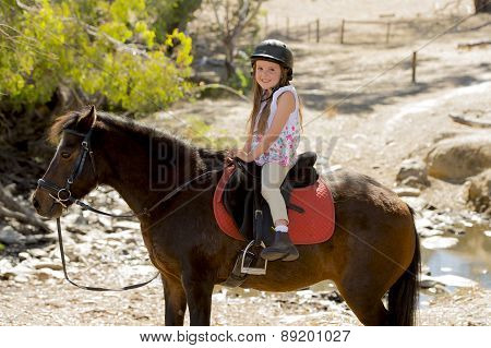 Sweet Young Girl 7 Or 8 Years Old Riding Pony Horse Smiling Happy Wearing Safety Jockey Helmet In Su