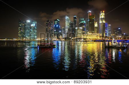 Brilliantly Lit Singapore Skyline From The Harbor At Night