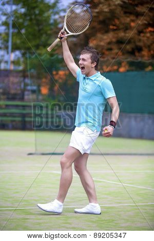 Tennis Sport Concept: Portrait Of Young Exclaiming Male Caucasian Tennis Player With Raquet Outdoors