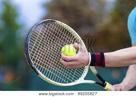 Closeup Of Hands Of Professional Male Tennis Player Holding Raquet And Tennis Ball In Contact.