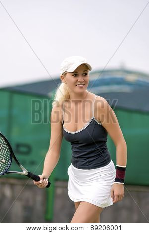 Professional Female Tennis Player With Raquet On Court Serving Ball. Positive Facial Expression