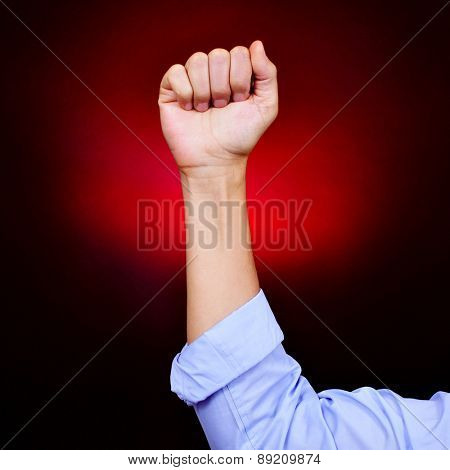 closeup of the raised fist of a young caucasian man on a black background red illuminated