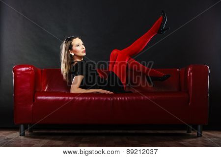 Elegant fashion outfit. Fashionable woman long legs in red vivid color pantyhose posing on couch indoor on black poster