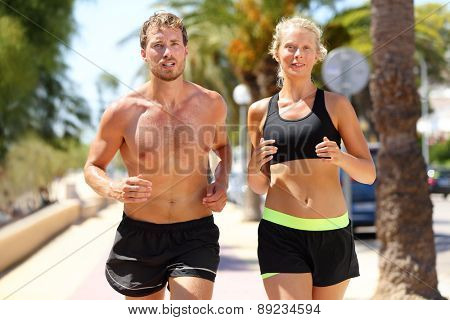 Sport people - active couple of runners running in city. Sexy fit young adults training cardio jogging under the summer sun sweating, man shirtless and woman in sports bra. Caucasian male and female.