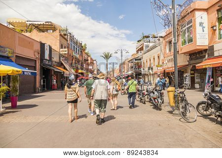 MARRAKESH, MOROCCO, APRIL 3, 2015: Tourists walk on Bab Agnaou street in direction of Jemaa el-Fnaa square