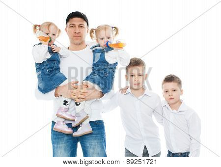 Family, dad holding his baby twin girls, babies drink from the bottle, standing next boys, isolation