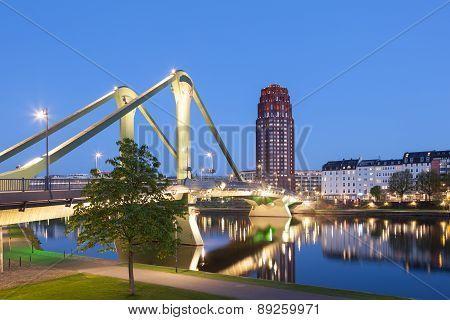 The old Floesser bridge illuminated at night in Frankfurt Main Germany poster