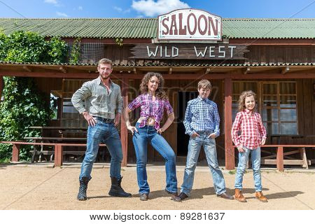 family of four posing on background of  wild west saloon