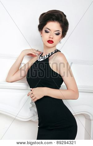 Fashion Beautiful Brunette Girl Model In Black Dress Posing Against The Wall. Makeup. Hairstyle. Att