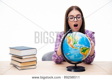 Amazed young female student sitting at the table and looking at globe over white background