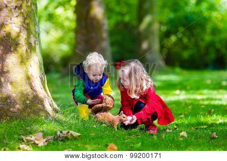 Kids Feeding Squirrel In Autumn Park