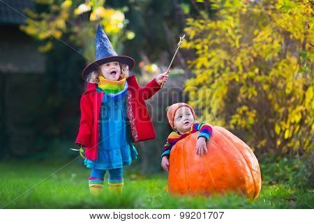 Little girl in witch costume and baby boy in huge pumpkin playing in autumn park. Kids at Halloween trick or treat. Toddler with jack-o-lantern. Children with candy bucket in forest. poster