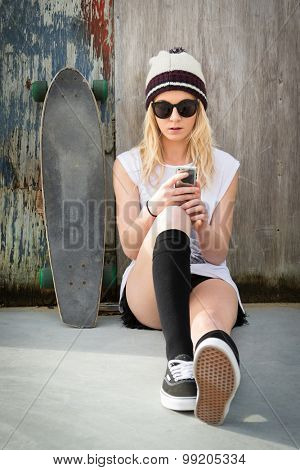 Pretty blond skater girl text messaging listening to music